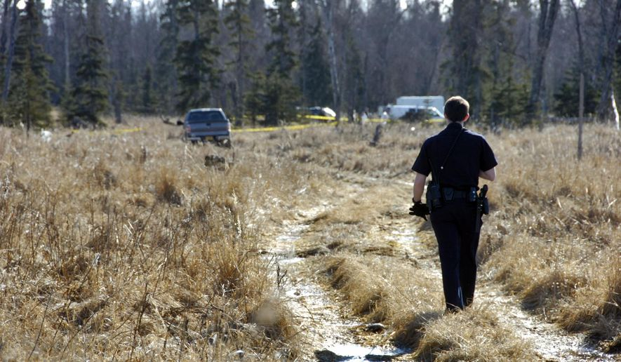 FILE - In this March 22, 2015 file photo, a Kenai, Alaska police officer walks down a trail leading to a temporary camp where investigators examine the remains of four people who had been missing for nearly 10 months from their Kenai home. An Alaska man shot and killed his girlfriend, her two young daughters and the family dog in 2014 before turning a gun on himself in the woods near the family's home, authorities said Wednesday, June 3, 2015. The determination came a year after the family disappeared in Kenai. (Rashah McChesney/Peninsula Clarion via AP, File)