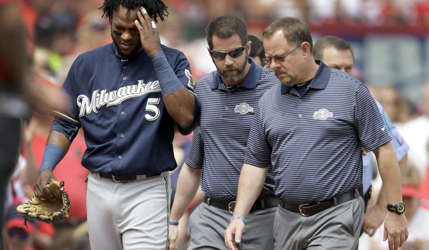 Milwaukee Brewers second baseman Hector Gomez (5) rubs his head as he is helped off the field by trainers after diving into the crowd after a foul ball by St. Louis Cardinals' Jason Heyward during the sixth inning of a baseball game, Wednesday, June 3, 2015, in St. Louis. Gomez left the game. (AP Photo/Jeff Roberson)