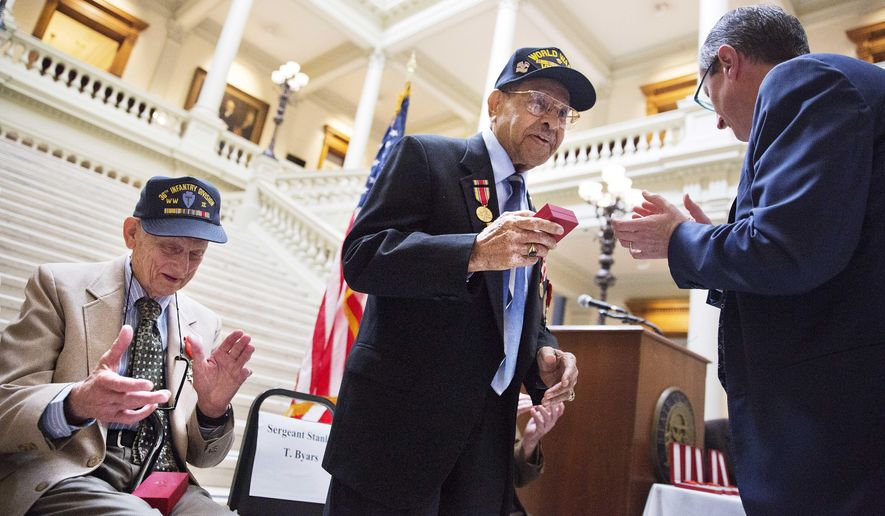 World War II veteran Stanley Byars, 92, of Atlanta, center, receives the French Legion of Honor medal from Denis Barbet, the consul general of France in Atlanta, right, as fellow veteran Neill Jack Cox, 90, of Clermont, Ga., left, applauds during a ceremony at the Capitol Thursday, June 4, 2015, in Atlanta. The Legion of Honor is the highest distinction France can award to a citizen or foreigner. The Ten WWII veterans who were honored Thursday fought on French territory as part of the liberation of the country from Nazi Germany and were nominated by President Francois Hollande. Regularly under enemy fire, Byars was the sole survivor of machine gun fire from a single German fighter plan that attacked his five-truck convoy. (AP Photo/David Goldman)