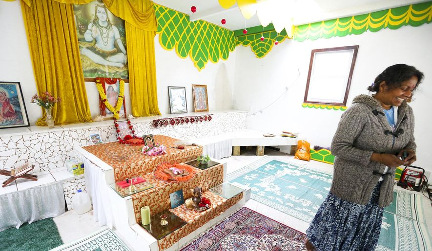 """ADVANCE FOR MONDAY, JUNE 8, 2015 - Satya Balroop show the temporary temple she and her family created in their garage on May 18, 2015, in Eagan, Minn. """"This space will always be here,"""" she said, """"for those who like a private moment during the day to come and meditate or get away from the rat race ... to just come and do their prayer."""" (Nikki Tundel/Minnesota Public Radio via AP)"""