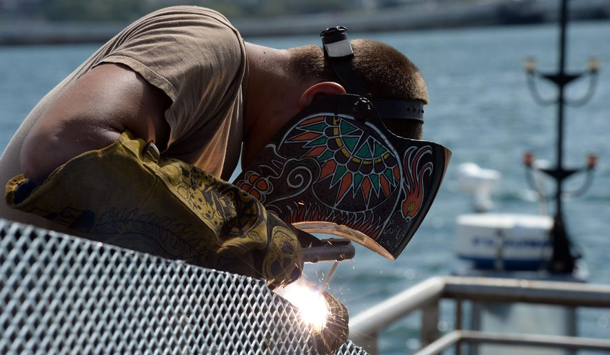 In this Wednesday, June 3, 2015, photo provided by the U.S. Navy, Hull Maintenance Technician 1st Class Robert French, assigned to Mobile Diving and Salvage Unit One, welds metal railings during the repairs of the floating dock next to the USS Arizona Memorial in Pearl Harbor, Hawaii.  Repairs to the damaged dock have been taking longer than expected, which will delay the reopening of the Pearl Harbor landmark at least a day, the navy and National Park Service said Wednesday.  (Mass Communication Specialist 2nd Class Laurie Dexter/U.S. Navy via AP)