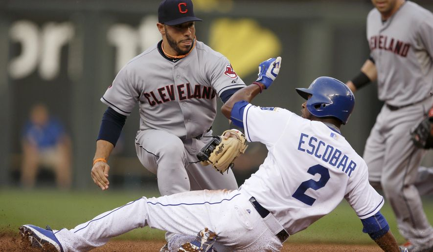Kansas City Royals' Alcides Escobar beats the tag by Cleveland Indians shortstop Mike Aviles, back, during the first inning of a baseball game at Kauffman Stadium in Kansas City, Mo., Thursday, June 4, 2015. Escobar stole second base on the play. (AP Photo/Orlin Wagner)