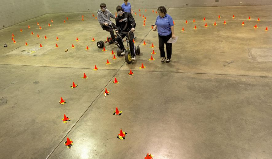 ADVANCE FOR USE SATURDAY, JUNE 6, AND THEREAFTER - In this April 29, 2015 photo, Department of Transportation employees Patty Ambrose, right, and Kathy Tolle, background, guide students through a course of cones in the Peoria  Civic Center exhibit hall as they ride tricycles while wearing goggles that demonstrate the effect of driving under the influence of alcohol  in Peoria, Ill. The Street Smart program incorporates graphic real-life images with frank discussion to help young drivers understand the consequences of choices they make behind the wheel. (David Zalaznik/Journal Star via AP)