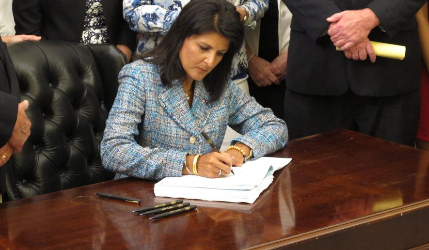 South Carolina Gov. Nikki Haley signs the state's new domestic violence bill into law on Thursday, June 4, 2015, in Columbia, S.C. The new law increases penalties for domestic violence and has a gun ban for batterers. (AP Photo/Jeffrey Collins)