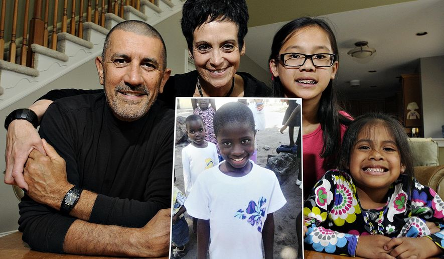 In this photo taken on May 9, 2014, Michael Fichera  and Linda Scotto with their two daughters Emma, 11, and 6-year-old Kearly, pose with a photograph of their adopted Congolese daughter, Miriam, at their home in Doylestown, Pa. The adoption process by the couple was virtually completed by the fall of 2013 and they were getting ready to travel to Congo when a suspension was imposed. Miriam, has continued to live in an orphanage; she'll turn 9 in August. After nearly two years of frustration, several hundred American families now have reason to hope that children they are adopting from Congo may finally be allowed to travel to the United States. (Rick Kintzel/The Intelligencer via AP)