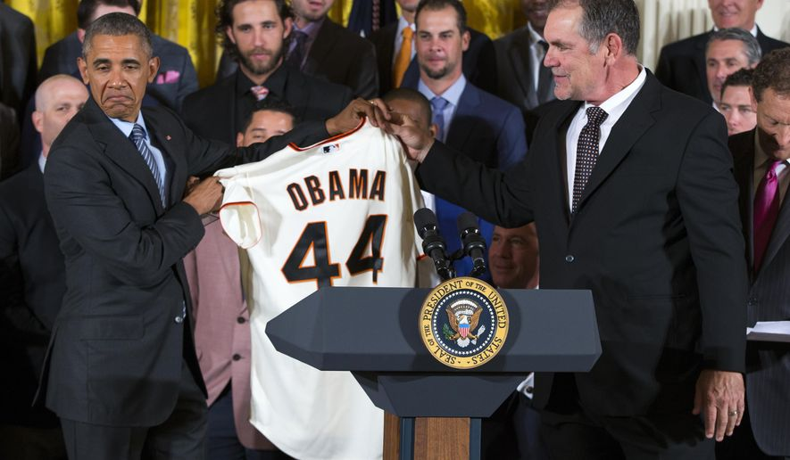 President Barack Obama accepts a personalized San Francisco Giants jersey from manager Bruce Bochy during an event in the East Room of the White House in Washington, Thursday, June 4, 2015, where the president honored the World Series champions.  (AP Photo/Evan Vucci)