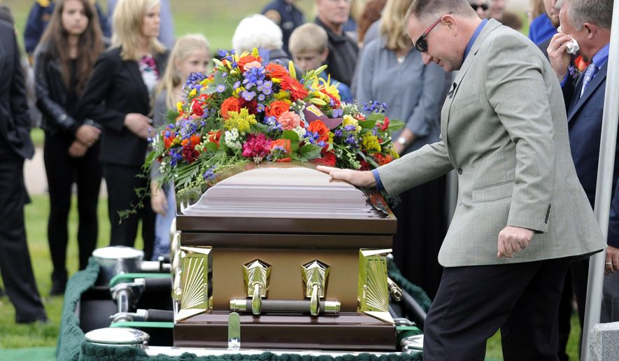 FILE - In this May 22, 2015 file photo, family and friends pay their respects as they pass by shooting victim John Jacoby's casket, at Lake View Cemetery in Windsor, Colo. Local police and the FBI are still investigating Jacoby's death, which officials say may be linked to two other shootings, the most recent being the late June 3, 2015 shooting death of a 65-year-old man in Loveland, Colo. (Joshua Polson/The Greeley Tribune via AP, file)