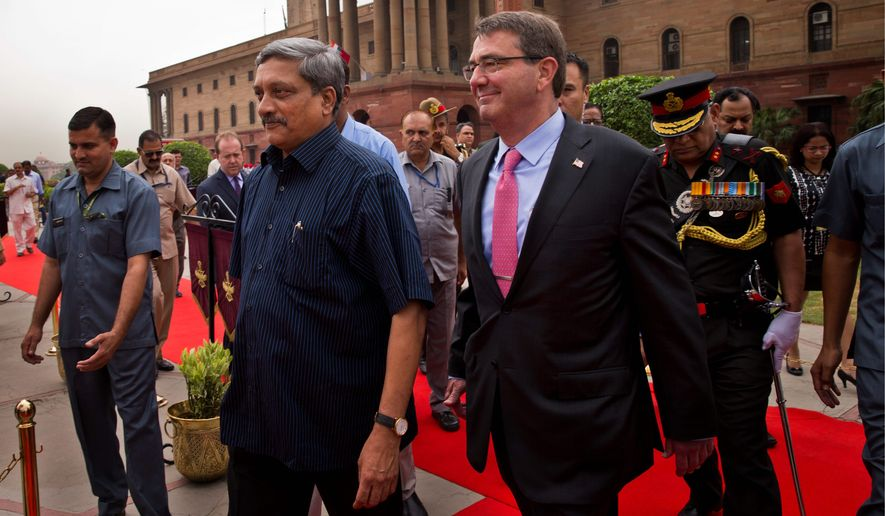 Defense Secretary Ashton Carter walks with Indian Defense Minister Manohar Parrikar after receiving a ceremonial welcome in New Delhi. Mr. Carter signed a 10-year agreement with India seen by some as a move to counter China's growing influence. (Associated Press)