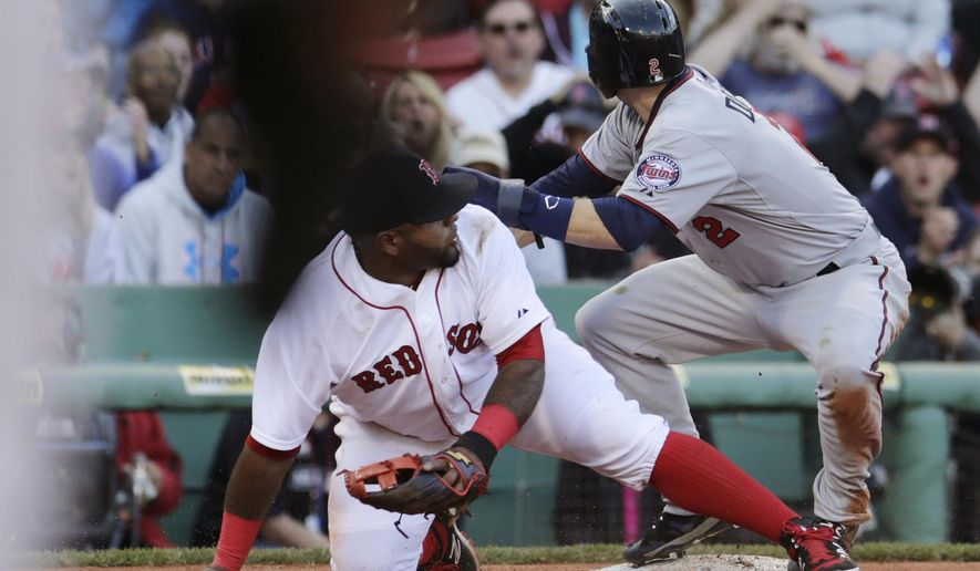 Boston Red Sox third baseman Pablo Sandoval drops to a knee after mishandling a throw from catcher Blake Swihart, which allowed Minnesota Twins' Brian Dozier, right, to score, breaking a 4-4 tie during the ninth inning of a baseball game Thursday, June 4, 2015, in Boston. The Twins defeated the Red Sox 8-4. (AP Photo/Charles Krupa)