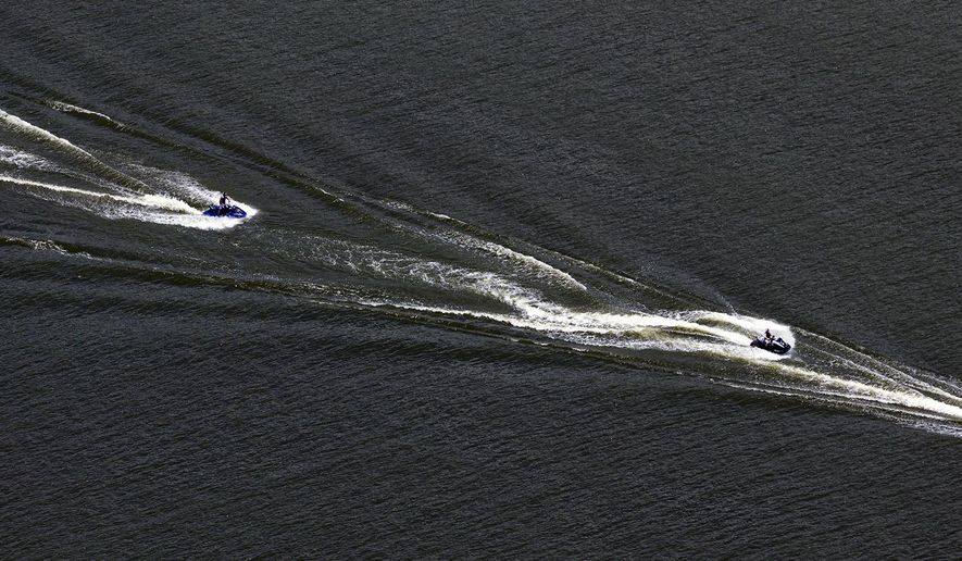 In this aerial photo taken on Sunday, May 31, 2015, a motor boat makes it way through Medina Lake, in Mico, Texas. Recent rains, though devastating for other parts of Central Texas, have been a blessing for the long-on-the-verge-of-empty lake. The Texas Water Development Board website reported the lake 48.4 percent full Sunday, up from a paltry 4.2 percent full one month ago. That translates to a 60 foot rise in the lake. (William Luther/The San Antonio Express-News via AP) RUMBO DE SAN ANTONIO OUT; NO SALES