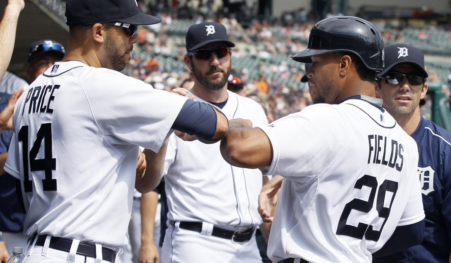 Detroit Tigers' Daniel Fields (29) celebrates with pitcher David Price (14) after scoring against the Oakland Athletics in the ninth inning of a baseball game at Comerica Park, Thursday, June 4, 2015, in Detroit. The Athletics defeated the Tigers 7-5. (AP Photo/Duane Burleson)
