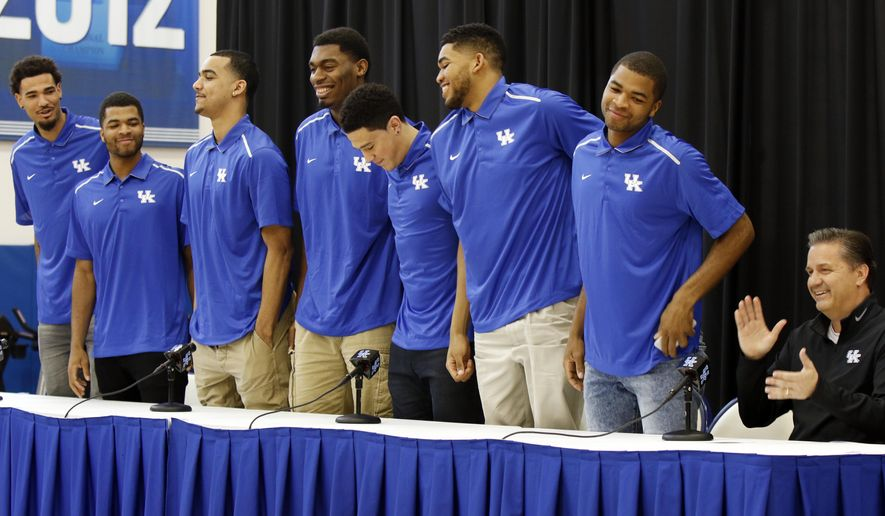 FILE - In this April 2015 file photo, Kentucky basketball coach John Calipari, right, applauds as players Willie Cauley-Stein, from left, Andrew Harrison, Trey Lyles, Dakari Johnson, Devon Booker, Karl-Anthony Towns and Aaron Harrison stand to announce their intent to enter the NBA draft during a news conference in Lexington, Ky. Calipari now faces the challenge of filling the void created after his top seven scorers entered the draft, including four possible lottery picks. (AP Photo/James Crisp, File)