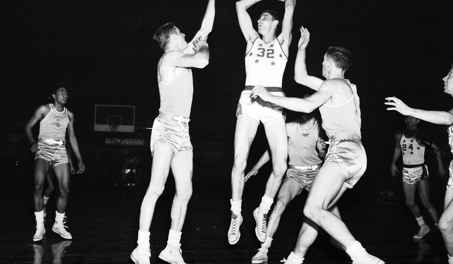 """FILE - In this March 1954 file photo, Clarence """"Bevo"""" Francis (32) of Rio Grande College, is guarded by Arizona State players during at the NAIA Men's Division I Basketball Tournament in Kansas City, Mo. Francis, who set college basketball records for high scoring in the 1950s, has died at 82. (AP Photo, File)"""
