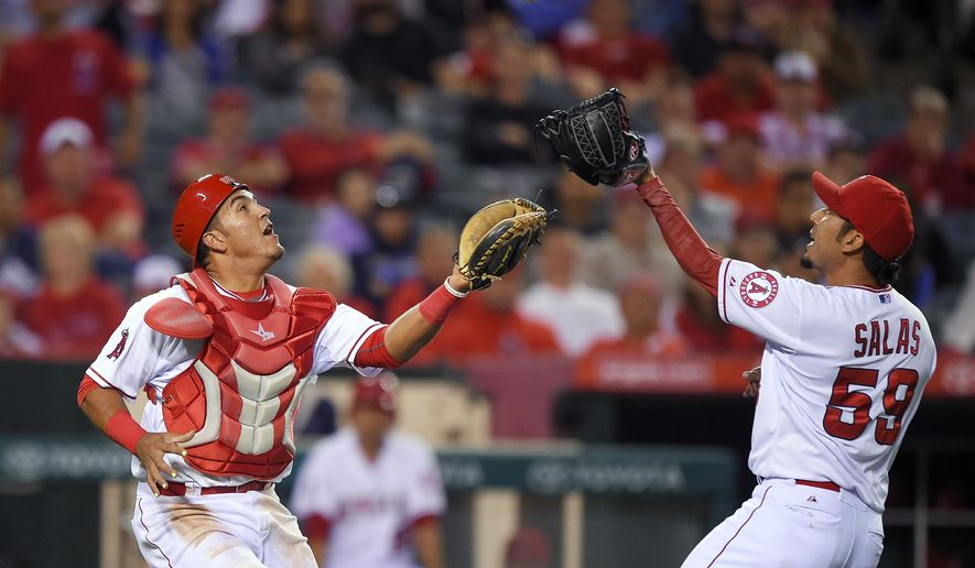 Los Angeles Angels relief pitcher Fernando Salas, right, makes the catch on a ball hit by Tampa Bay Rays' Steven Souza Jr. before colliding with catcher Carlos Perez during the eighth inning of a baseball game, Wednesday, June 3, 2015, in Anaheim, Calif. (AP Photo/Mark J. Terrill)