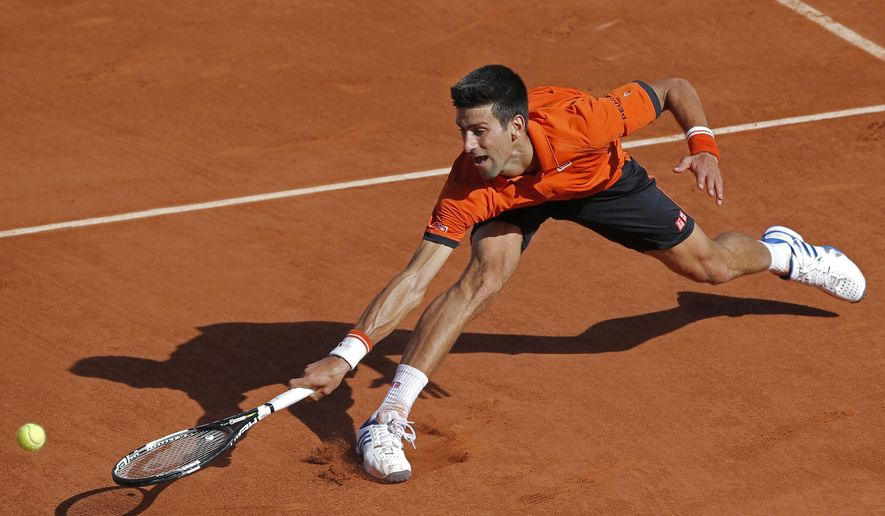 Serbia's Novak Djokovic returns in the quarterfinal match of the French Open tennis tournament to defeat Spain's Rafael Nadal in three sets, 7-5, 6-3, 6-1, at the Roland Garros stadium, in Paris, France, Wednesday, June 3, 2015. (AP Photo/Christophe Ena)