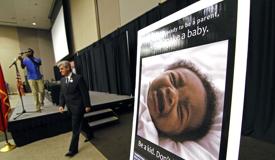 Gov. Phil Bryant walks past one of several new posters that will be distributed statewide to schools calling to mind the responsibilities of being a teen parent, Thursday, Dec. 6, 2012, during the First Annual Teenage Pregnancy Prevention Summit in Jackson, Miss. (AP Photo/Rogelio V. Solis) ** FILE **