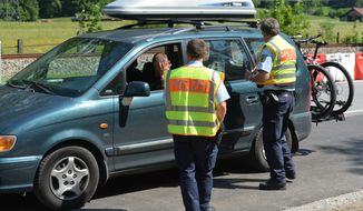 Police check a car driver ahead of the G-7 summit on the main road between Mittenwald in Germany and Scharnitz in Austria, in southern Germany, Thursday, June 4, 2015. The summit will take place June 7/8 on Schloss Elmau hotel near Garmisch-Partenkirchen. (AP Photo/Kerstin Joensson)
