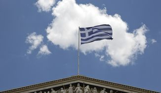 The Greek flag flies at the top of the Athens Academy building, in Athens,  Thursday, June 4, 2015 .Greece remains at loggerheads with creditors over key economic reforms after a meeting between Prime Minister Alexis Tsipras and the head of the European Union's executive arm failed to yield a breakthrough on the release of vital bailout loans. (AP Photo/Petros Giannakouris)