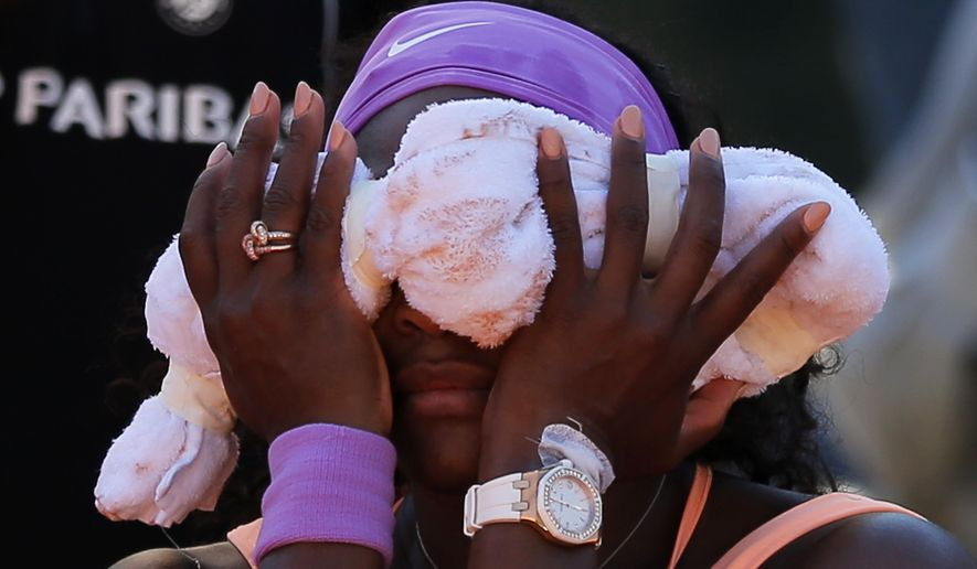 Serena Williams of the U.S. cools off with a towel in her semifinal match of the French Open tennis tournament against Timea Bacsinszky of Switzerland at the Roland Garros stadium, in Paris, France, Thursday, June 4, 2015. (AP Photo/Francois Mori)