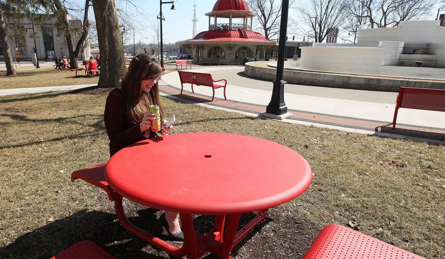ADVANCE FOR USE SUNDAY, JUNE 7, 2015 AND THEREAFTER - In this March 11, 2015 photo, Cari Rutherford spends her lunch break at Central Park in Decatur, Ill. Despite major fires, never-ending renovation projects and a changing cast of businesses, Decatur's Central Park has remained a symbolic heart for the community's art and social scene. In the center of downtown, the nearly 150-year-old park has seen its share of everything from marching bands, art festivals, the centerpiece for Decatur Celebration and sometimes just a quiet spot for residents to enjoy lunch. (Jim Bowling/Herald & Review via AP)
