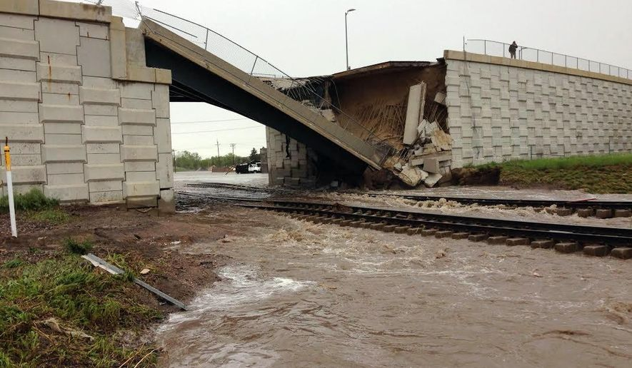 This photo provided by the Wyoming Highway Patrol shows a portion of a bridge over railroad tracks on the north side of the small eastern Wyoming town of Lusk that was collapsed by flash flood waters early Thursday. June 4, 2015. Up to 6 inches of rain fell in the area overnight Wednesday and early Thursday, forcing some residents to leave their homes and causing damage to area highways. (Wyoming Highway Patrol via AP))