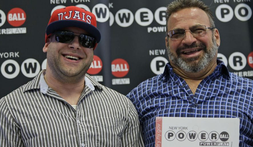 Anthony Perosi, right, holding a copy of the winning power ball ticket and his so Anthony Perosi III smile during a ceremony in which New York's Lottery Yolanda Vega  presented an over-sized $136,000,000 prize check to the Staten Island plumber, Thursday, June 4, 2015, in New York.  (AP Photo/Mary Altaffer)