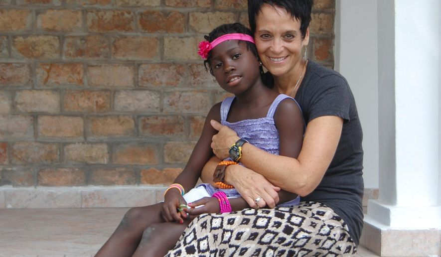 In this photo provided by Linda Scotto, Linda Scotto poses with her adopted daughter Miriam in October 2014 at Sunny Day guesthouse in Kinshasa, Congo. The adoption process by Scotto and and Michael Fichera of Doylestown, Pa., was virtually completed by the fall of 2013 and the couple were getting ready to travel to Congo when a suspension was imposed. Miriam, has continued to live in an orphanage; she'll turn 9 in August. After nearly two years of frustration, several hundred American families now have reason to hope that children they are adopting from Congo may finally be allowed to travel to the United States. (Courtesy of Linda Scotto via AP)