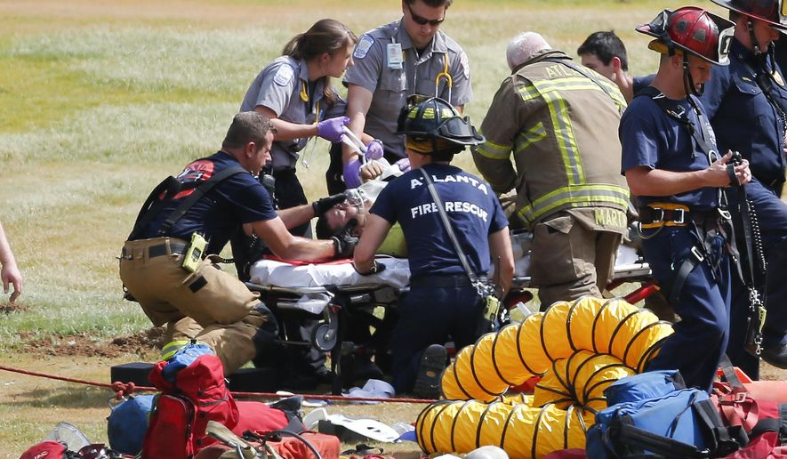 A man is treated by Atlanta Fire and Rescue personal after being pulled from a manhole on the Georgia Tech golf course  Thursday, June 4, 2015, in Atlanta. The man and another worker had to be rescued after becoming trapped in the hole. A fire department spokeswoman said both were breathing and conscience and were transported to a local hospital.  (AP Photo/John Bazemore)