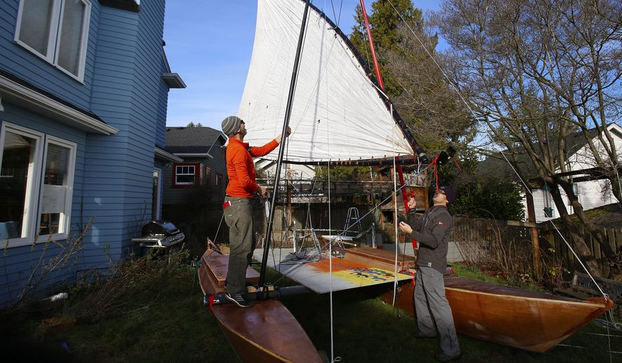 In this Jan. 8, 2015,  photo, Thomas Nielson and Scott Veirs build a catamaran in their garage in Seattle.  Using only their wits, the wind and lots of muscle power, dozens of people were scheduled to set off early Thursday, June 4, 2015,  on Stage 1 of a 750-mile ocean-going race that weaves its way up the Inside Passage, a treacherous coastal waterway through a spackling of islands known for its dramatic tidal changes and spectacular scenery.  (Mark Harrison/The Seattle Times via AP) SEATTLE OUT; USA TODAY OUT; MAGS OUT; TELEVISION OUT; NO SALES; MANDATORY CREDIT TO BOTH THE SEATTLE TIMES AND THE PHOTOGRAPHER