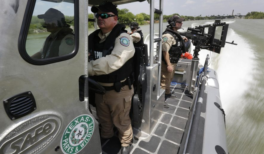 FILE - In this July 24, 2014, file photo, Texas Parks and Wildlife Wardens patrol the Rio Grand on the U.S.-Mexico border in Mission, Texas. Wardens across the state have been tasked with weeklong border rotations as part of Operation Strong Safety _ a joint effort among federal, state and local law enforcement agencies to increase border security introduced by then-Gov. Rick Perry a year ago this month. (AP Photo/Eric Gay, Pool, File)
