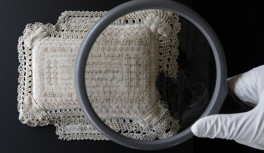 A member of museum staff holds a magnifying glass as he poses for a photograph with a pin-cushion from 1879 embroidered with human hair by Anne Parker who was arrested over 400 times for alcohol related offences, and forms part of the forthcoming The Crime Museum Uncovered exhibition at the Museum of London in London, Thursday, June 4, 2015. The exhibition will display objects from the Metropolitan Police's Crime Museum which were previously only accessible to police professionals and invited guests. (AP Photo/Tim Ireland)