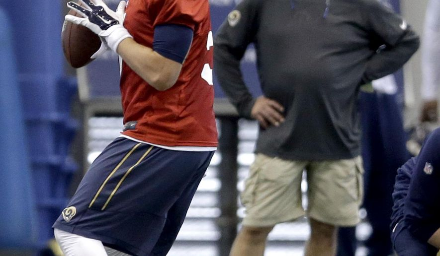 St. Louis Rams quarterback Nick Foles, left, looks to throw as Rams head coach Jeff Fisher watches during an NFL football organized team activity, Thursday, June 4, 2015, in St. Louis. (AP Photo/Jeff Roberson)