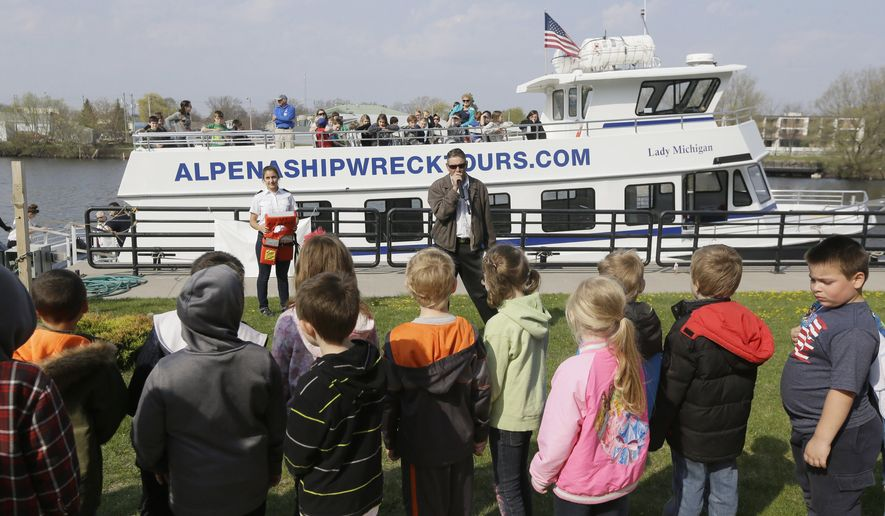 In a photo from Thursday, May 7, 2015,  in Alpena, Mich., students wait to board the Lady Michigan for a shipwreck tour in Thunder Bay. Thunder Bay National Marine Sanctuary is rolling out the buoys and starting another season of work on Lake Huron _ the highlight of which is searching for and studying shipwrecks. (AP Photo/Carlos Osorio)