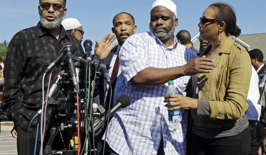 Ibrahim Rahim, second from right, brother of shooting victim Usaama Rahim, reacts with a relative during a news conference Thursday, June 4, 2015, in Boston's Roslindale neighborhood in the area where Rahim was shot to death. Police said Usaama Rahim had lunged at members of the Joint Terrorism Task Force with a knife when they approached to question him. (AP Photo/Elise Amendola)