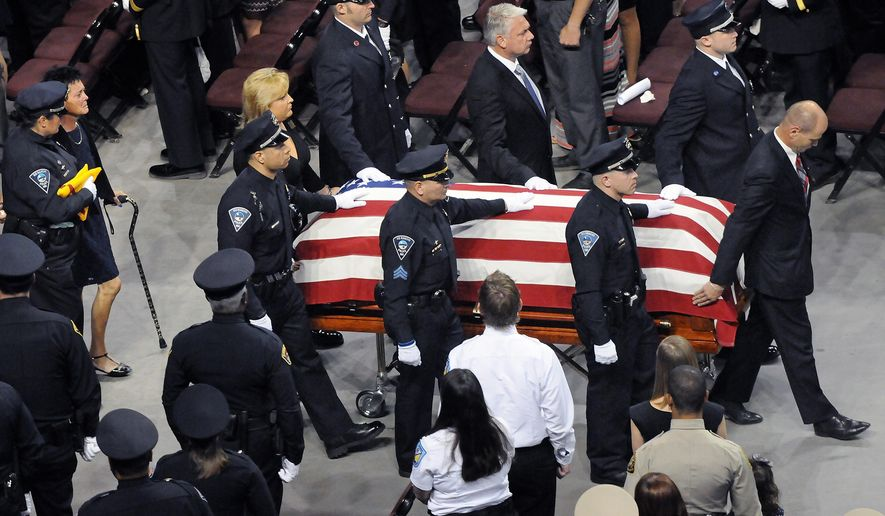 Pall bearers walk beside of the flag draped coffin of Rio Rancho Officer Gregg Benner followed by his wife Julie Ann Benner and officer Lana Elder as they leave the arena at the Santa Ana Center in Rio Rancho, N.M., Thursday, June 4, 2015. Hundreds of law enforcement officers from throughout New Mexico and beyond gathered with community and family members to pay their last respects to the Rio Rancho police officer who was shot and killed during a May 25 traffic stop. (Jim Thompson/The Albuquerque Journal via AP)
