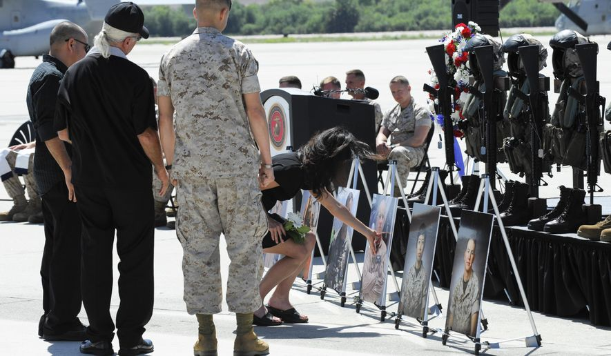 """People pay their respects after a memorial service held at Camp Pendleton, Calif., Wednesday, June 3, 2015, for six Marines who were killed in a helicopter crash while helping with disaster relief in earthquake-devastated Nepal. Hundreds of people attended the ceremony to honor the six who were aboard the U.S. military's UH-1 """"Huey"""" that went down on a steep mountainside near the town of Charikot on May 12. (AP Photo/Denis Poroy)"""