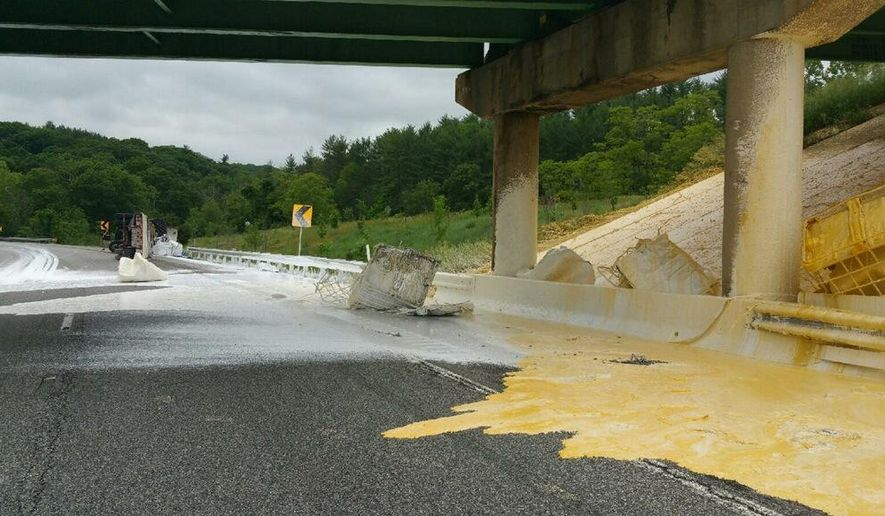 This photo provided by Maryland State Highway Administration shows gallons of white and yellow paint coating parts of Interstate 68 near Hancock, Md., on Wednesday, June 3, 2015, after a tractor-trailer overturned. Police have charged the driver with using a handheld cellphone while driving. Officials say cleanup will take several days. (David Buck/Maryland State Highway Administration via AP)