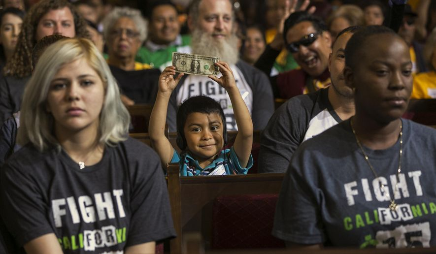 David Lazo, 5, center, with his father Francisco, right, raises a dollar bill as workers await the Los Angeles City Council's vote to raise the minimum wage in the city to $15 an hour by 2020 in Los Angeles Wednesday, June 3, 2015. The Los Angeles City Council has voted 13-1 to raise the minimum wage to $15 an hour by 2020, but a second vote is required. The ordinance tentatively approved Wednesday had the endorsement of Mayor Eric Garcetti. A final vote will be taken June 10 because the action Wednesday was not unanimous. The increases would begin with a wage of $10.50 in July 2016, followed by annual increases to $12, $13.25, $14.25 and then $15. Small businesses and nonprofits would be a year behind. (AP Photo/Damian Dovarganes)