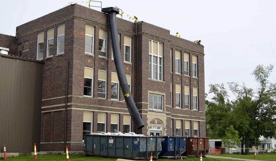 In this photo taken on Thursday, June 4, 2015, construction crews work on repairing South Central Calhoun High School in Lake City, Iowa. Board members approved four construction-related bids Thursday morning to fix up the school following a tornado last month. (Peter Kaspari/The Messenger via AP)