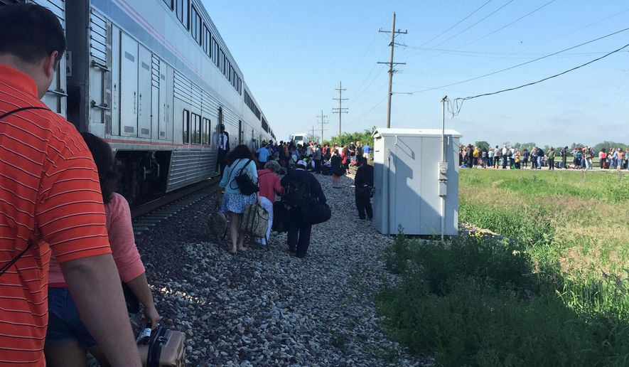 People gather following a train collision near Wilmington, Ill., Friday, June 5, 2015. The Amtrak train was headed to Chicago from San Antonio and slammed into a semitrailer at a crossing. (Sam Herwitz via AP)