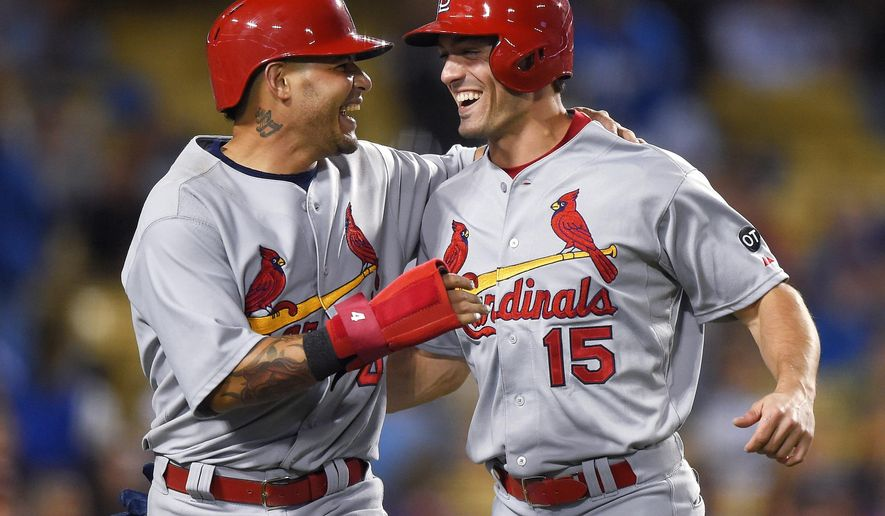 St. Louis Cardinals' Yadier Molina, left, and Randal Grichuk celebrate after scoring on a double by Kolten Wong during the eighth inning of a baseball game against the Los Angeles Dodgers, Thursday, June 4, 2015, in Los Angeles. (AP Photo/Mark J. Terrill)