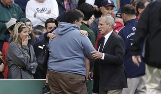 Boston Red Sox president and CEO Larry Lucchino comforts a man holding a child after a woman they were sitting with was hit by a wooden shard, off a broken bat of Oakland Athletics' Brett Lawrie, in the second inning during a baseball game at Fenway Park in Boston, Friday, June 5, 2015. The game stopped as the woman was taken from the stands on a stretcher down the first base line to a waiting ambulance. (AP Photo/Charles Krupa)