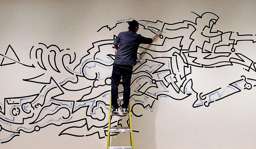 "Yoon Hyup paints a mural in the Dennos Museum Center in Traverse City for the museum's upcoming exhibit ""Sideways: Exploring Skateboard Art + Culture,"" which opens on May 31, 2015. (Jan-Michael Stump/Traverse City Record-Eagle via AP) MANDATORY CREDIT"