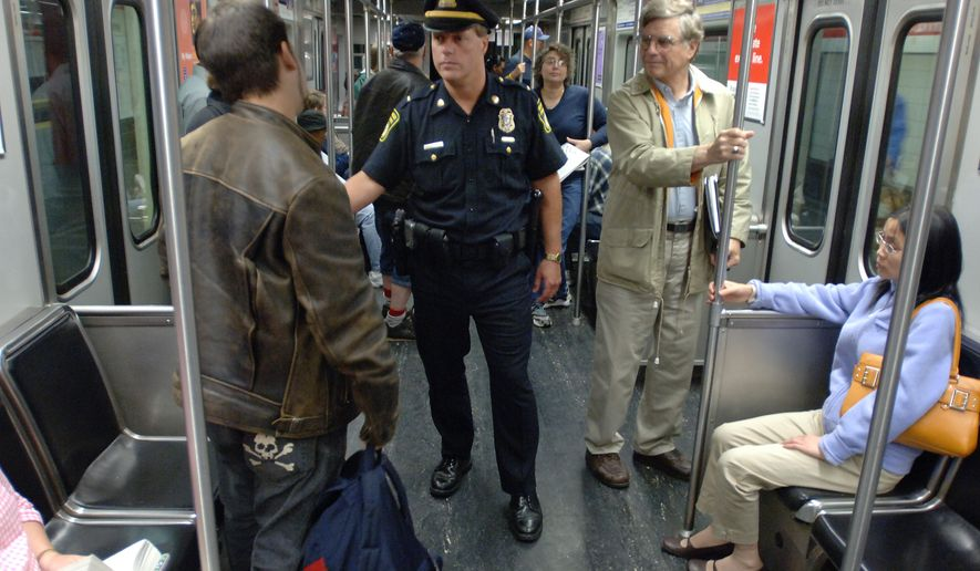 MBTA Transit Police Lt. Gary Fredericks, center, speaks to a commuter on the Red Line subway in Boston, Thursday, July 7, 2005, after Massachusetts authorities raised security at mass transit stations to orange alert status in response to earlier bombings in London. (AP Photo/Josh Reynolds)