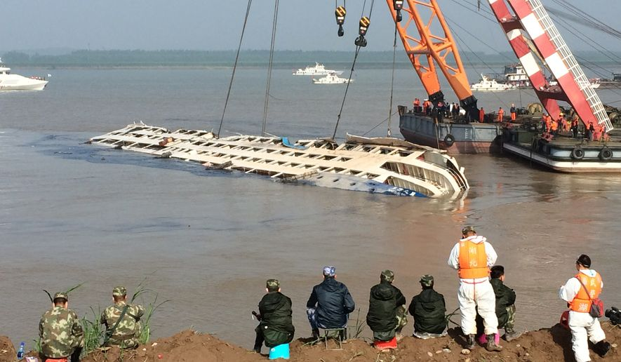 Cranes attempt to right the capsized tourist ship Eastern Star in Jianli county in southern China's Hubei province Friday, June 5, 2015. Top-deck cabins poked out of the water from the capsized river cruise ship on the Yangtze on Friday after disaster teams righted the vessel to quicken the search for the hundreds still missing. (Chinatopix Via AP) CHINA OUT