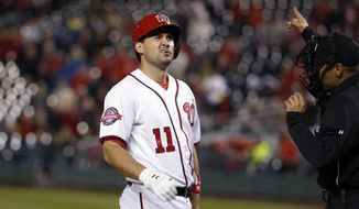 Washington Nationals first baseman Ryan Zimmerman reacts after being hit by a pitch as home plate umpire Gabe Morales points to first base during the sixth inning of the Nationals' baseball game against the Chicago Cubs at Nationals Park, Thursday, June 4, 2015, in Washington. The Cubs won 2-1. (AP Photo/Alex Brandon)