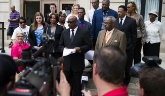 "Pastors, water activists, a city councilman and an attorney stand at the steps outside of the Genesee County Circuit Court in Flint after filing a lawsuit Friday, June 5, 2015, that alleges the city ""recklessly endangered""  the health and safety of its residents when it stopped purchasing drinking water from Detroit and began treating Flint River water as its primary source. (Jake May/The Flint Journal-MLive.com via AP)"
