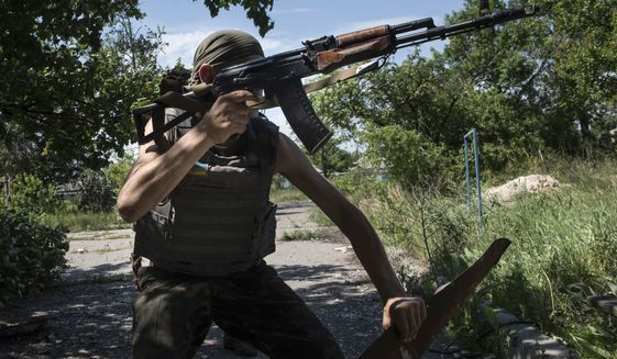 A Ukrainian serviceman patrols the area near the division line with separatists in Marinka, near Donetsk, eastern Ukraine, Friday, June 5, 2015. As fears persist that eastern Ukraine is about to fall back into full-scale war, a leader of the international monitoring group is urgently calling for resumed negotiations. (AP Photo/Evgeniy Maloletka)
