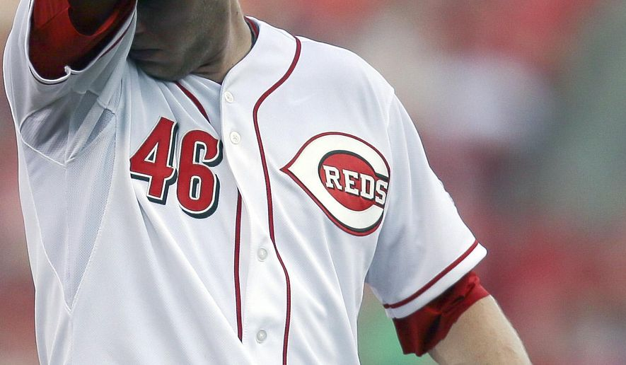 Cincinnati Reds starting pitcher Jon Moscot wipes his head after giving up two runs in the first inning of a baseball game against the San Diego Padres, Friday, June 5, 2015, in Cincinnati. (AP Photo/John Minchillo)