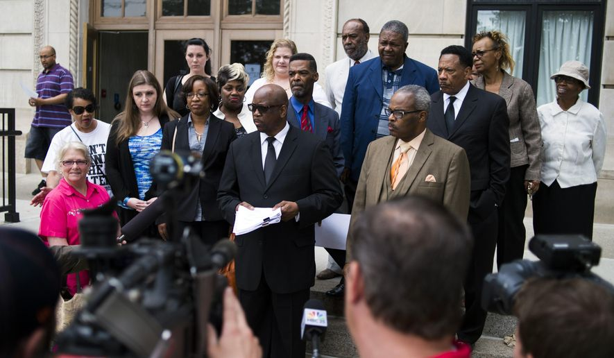 """Pastors, water activists, a city councilman and an attorney stand at the steps outside of the Genesee County Circuit Court in Flint after filing a lawsuit Friday, June 5, 2015, that alleges the city """"recklessly endangered""""  the health and safety of its residents when it stopped purchasing drinking water from Detroit and began treating Flint River water as its primary source. (Jake May/The Flint Journal-MLive.com via AP)"""